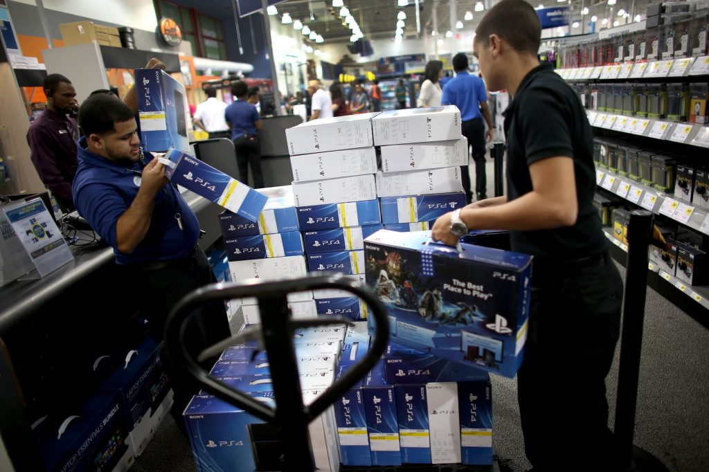 PEMBROKE PINES, FL - NOVEMBER 15:  Anthony Feliz (L), sales associate, and Isaiah Amaro, sales support, unload a supply of Sony Playstation 4 consoles at Best Buy after they went on sale at midnight on November 15, 2013 in Pembroke Pines, Florida. PlayStation 4 is the follow-up to the company's PlayStation 3 and is priced at $400.  (Photo by Joe Raedle/Getty Images)